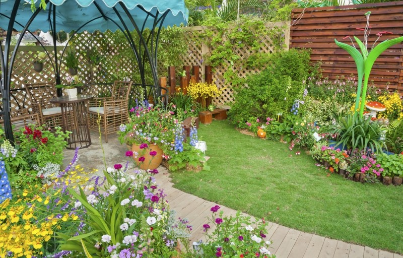 lush compact landscaped backyard flower garden with flowerbed and
