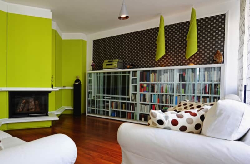 Modern Living Room In An Apartment With Bold Lime Green Walls And Full Length Bookcase Cabinet