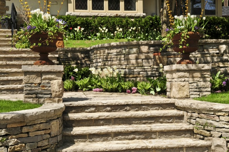 Natural stone landscaped pathway and retaining wall in front of a house