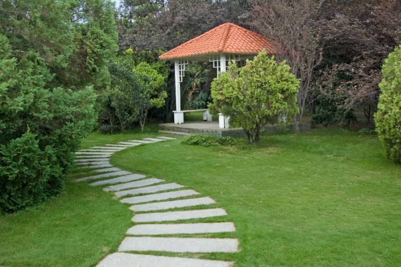 Beautiful summerhouse and landscaped curved walkway in the gardenBeautiful summerhouse and landscaped curved walkway in the garden