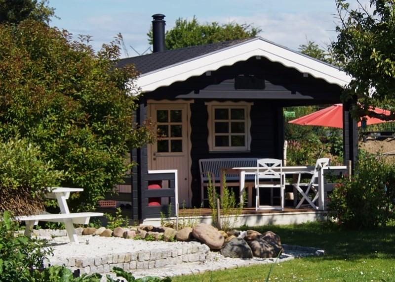 Wooden bungalow cabin painted black and set in a beautiful garden