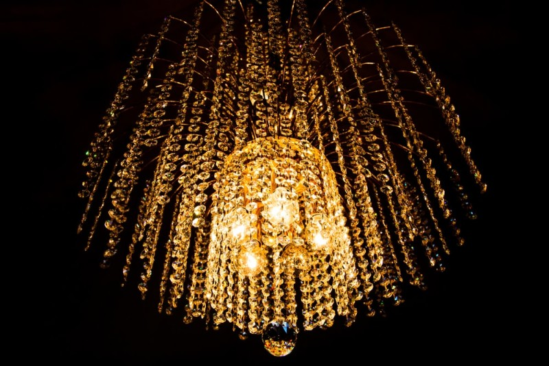 High End Chandeliers and Unique Crystal Chandeliers:Crystal chandelier glowing with a golden light against a dark background,Lighting