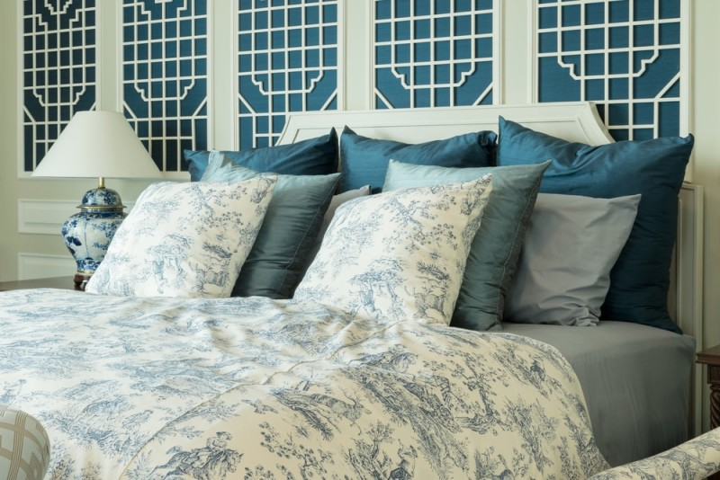 classic style bedroom with blue pillows and chinese lamp style on bedside table min e1437857616682 - Blue and White Interiors