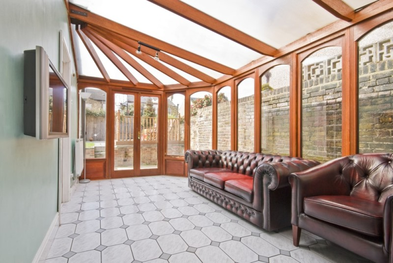 conservatory extension of a family home with leather sofa and tiled floor min e1436698953456 - 15 Fantastic Modern Conservatories and Sunroom Makeover Ideas