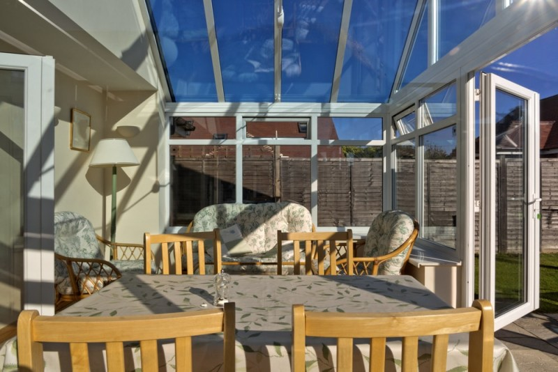 conservatory tables chairs plants room in house next to garden min e1436696783656 - 15 Fantastic Modern Conservatories and Sunroom Makeover Ideas