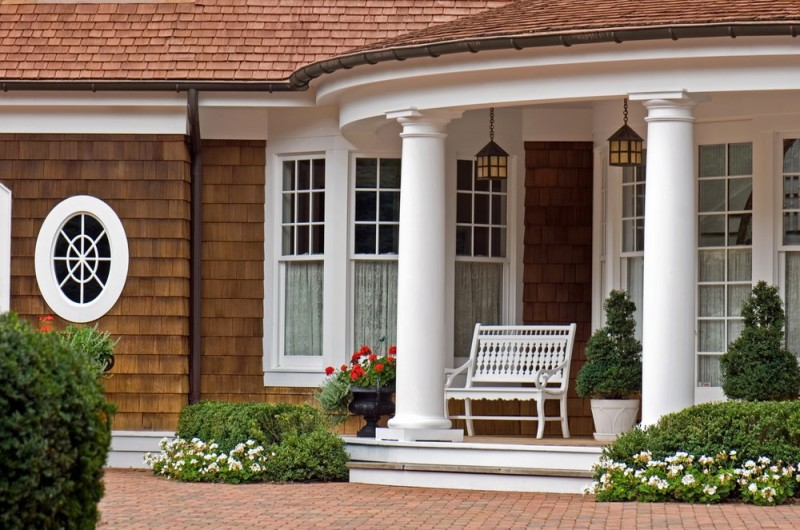 fancy front porch of stately summer home with two large columns - House Front Porch