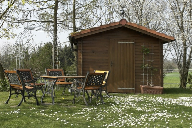 Idyllic summer house and garden room with outdoor furniture at spring time