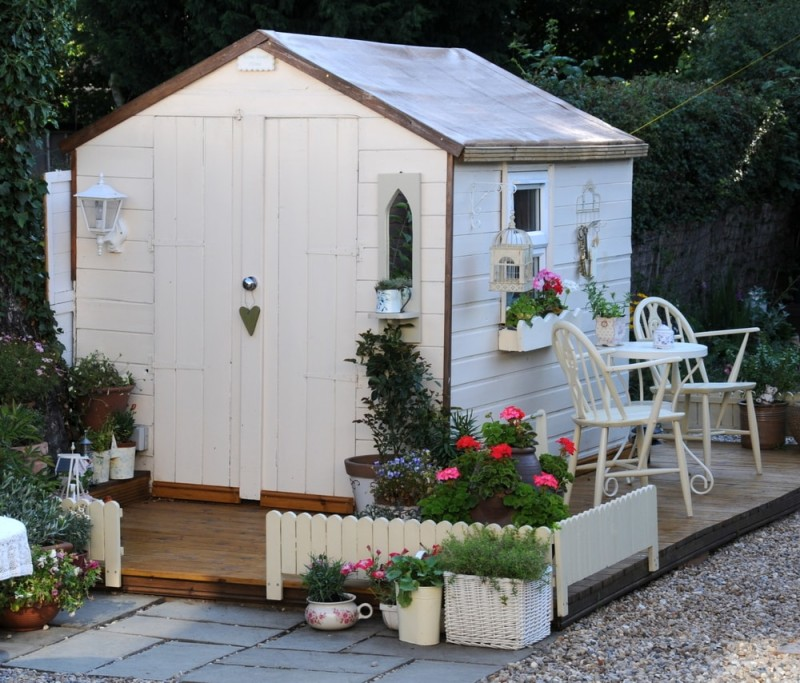 Pretty garden room shed with tiny windows, big door and outdoor seating