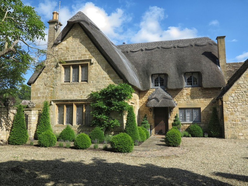 Beautiful old stone cottage with thatched roof in the village of Chipping Campden in England