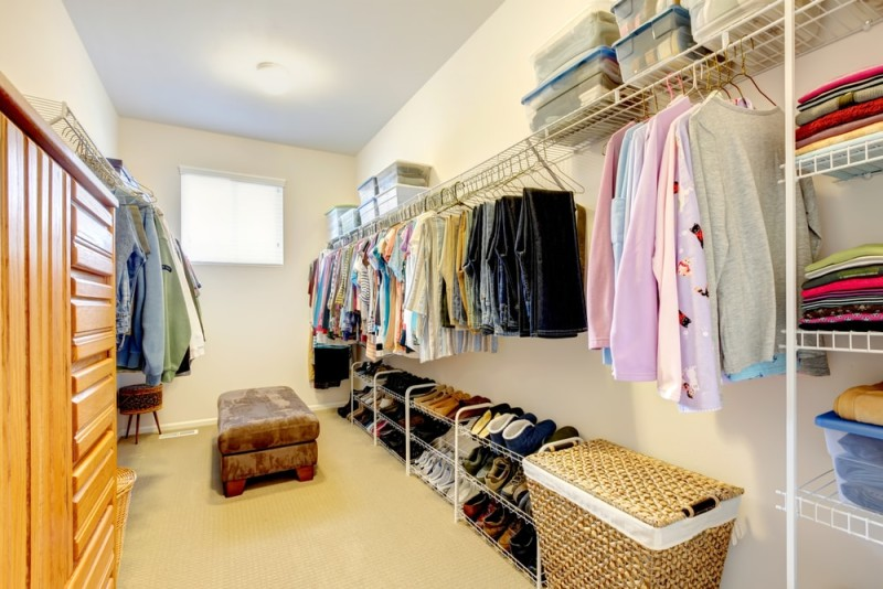 Big walk-in closet with wooden dresser and shelves and hangers for clothes and shoes