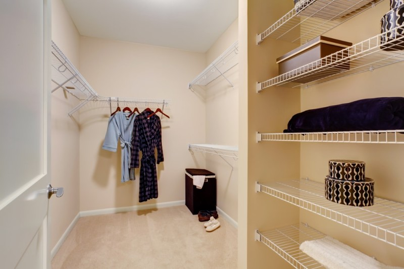 Light color tones feature in this walk-in closet with shelves