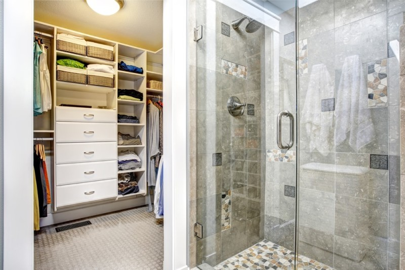 Modern bathroom interior with glass door shower and walk-in closet wardrobe