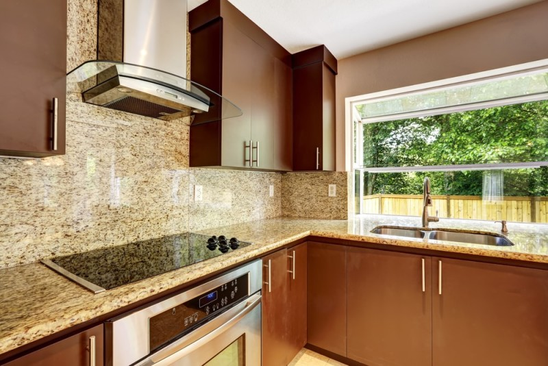 Modern kitchen room with matte brown cabinets shiny granite tops steel stove with hood and granite back splash min e1440203765763 - Striking Kitchen Backsplash Ideas & Pictures
