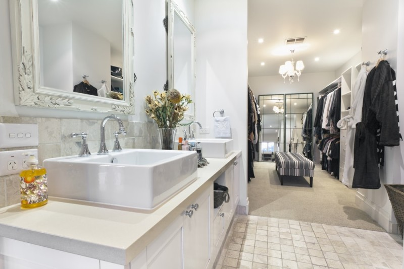 Stylish master bathroom with twin sinks and spacious walk in closet wardrobe