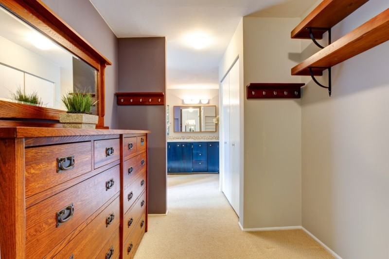 Walk in closet with rich beautiful wooden dresser and bathroom in the background
