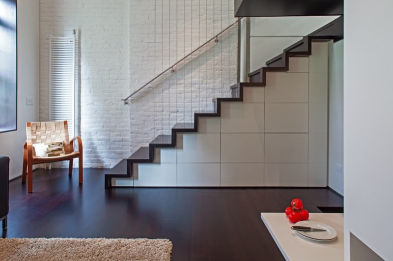 Modern staircase with under stair cabinets and storage and painted brick wall