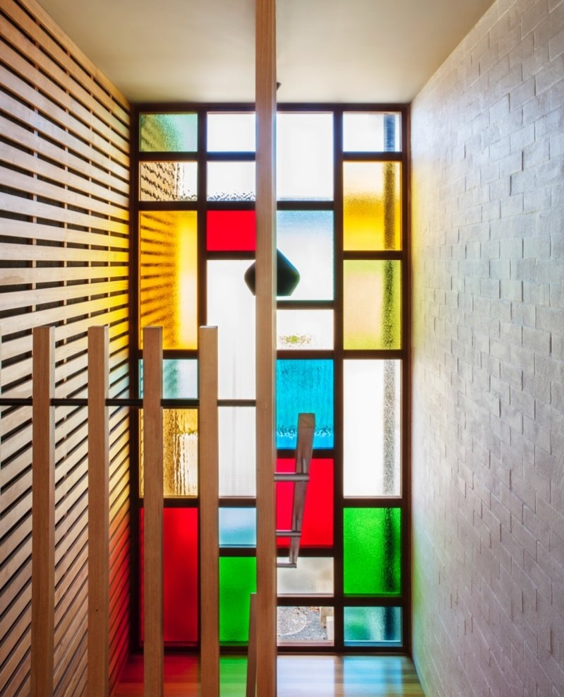 Stairwell with stained glass window wall and cedar slats adjoining the painted old brick wall