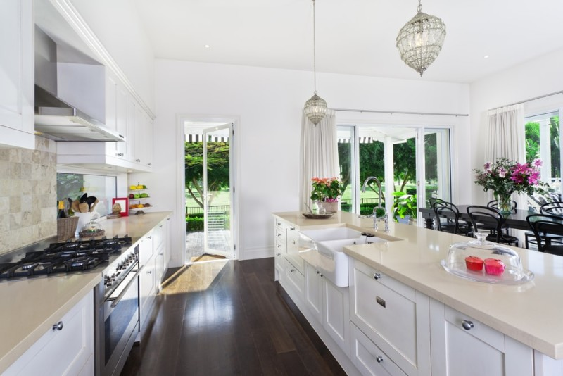 Stylish Open Plan Kitchen With Stainless Steel Appliances And Dining Area  Overlooking A Pool And Golf