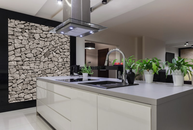 Beautiful white kitchen island with decorative stone wall.