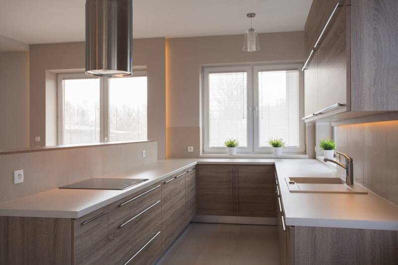 Compact kitchen with light coloured cupboards and white counter tops.
