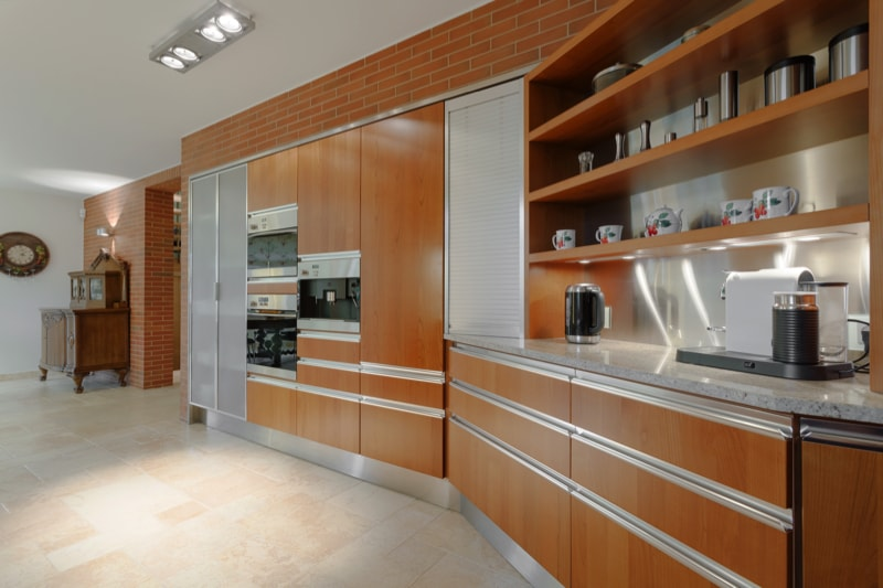 Luxury apartment showing an angled kitchen with a set of wooden cabinets and stainless steel appliances