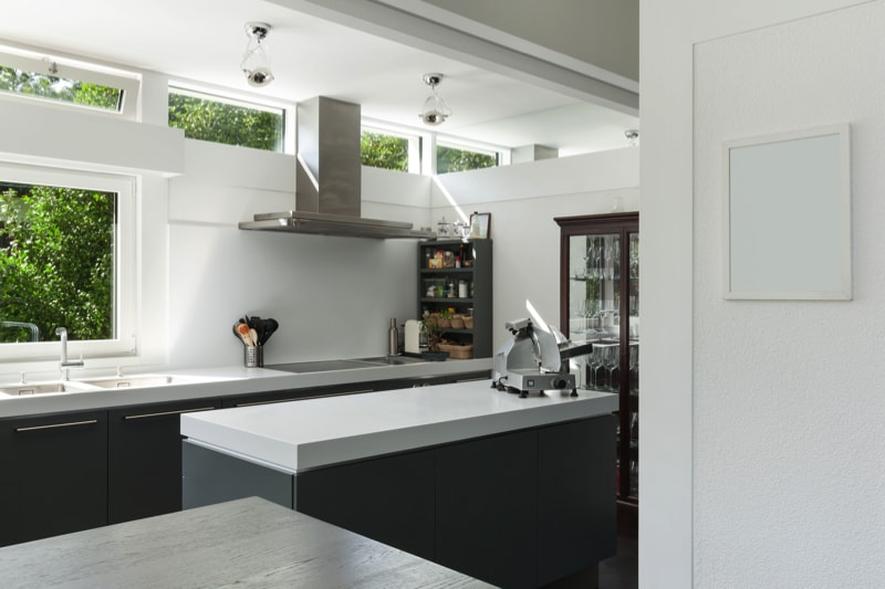 Modern kitchen with charcoal grey cabinets and crisp white benches