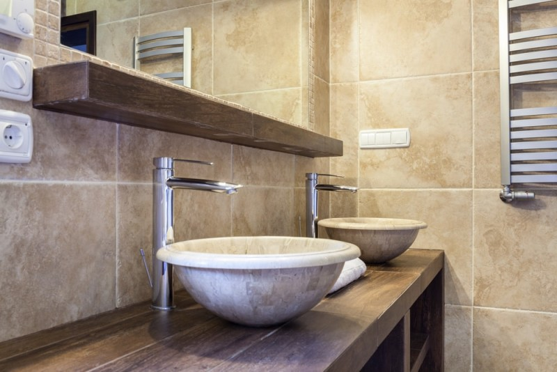 Interior of an expensive tiled bathroom with twin marble washbasins. Bathroom Wash Basins