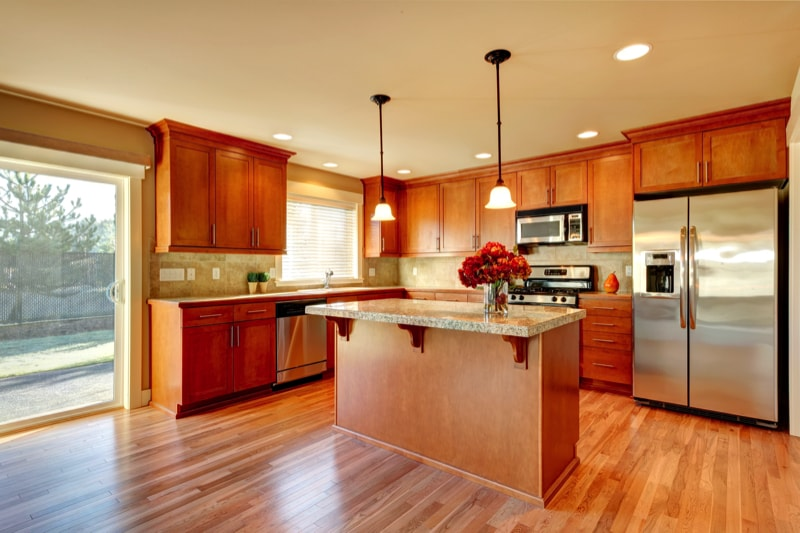 Bright kitchen with hardwood floor wood cabinets and modern steel appliances and tile back splash.