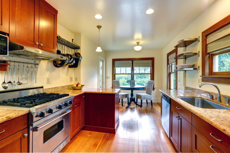 Galley style kitchen with wooden cabinets and marble counter top