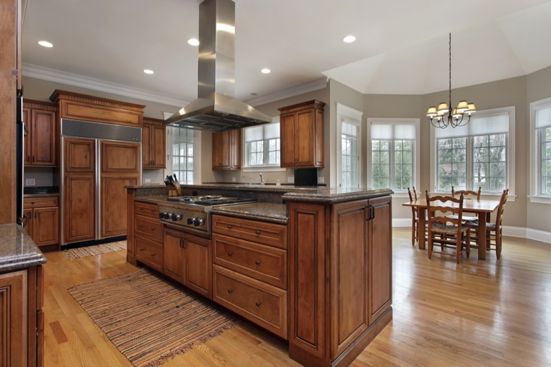 Kitchen in luxury home with wood and granite island with range hood over the island bench.
