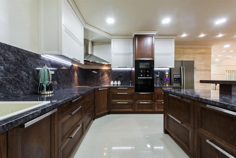 Spaciously designed kitchen with wood cabinets and a dark grey marble counter top.