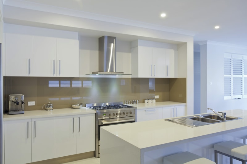 Modern white kitchen with stainless steel appliances and large glass splash back