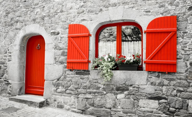 Old stone house with red wooden shutters and red door. Boxes with red and white & Red Doors on Houses