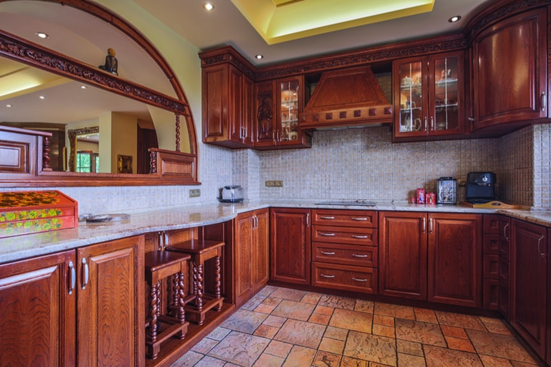 Spacious wooden kitchen interior with tiled splash back and floor.