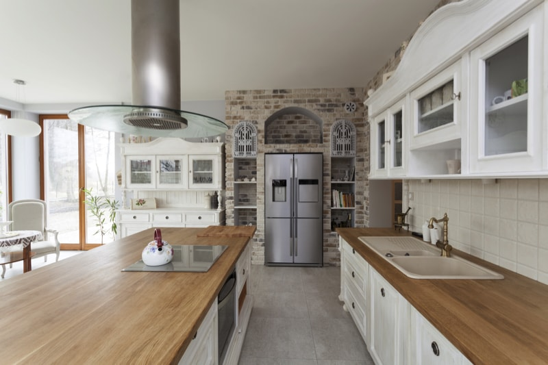 Tuscany Style kitchen with brick, white cabinets and a wooden counter top