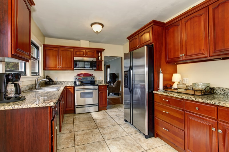 Well defined kitchen with large tile floor, stained timber cabinets and stainless steel appliances