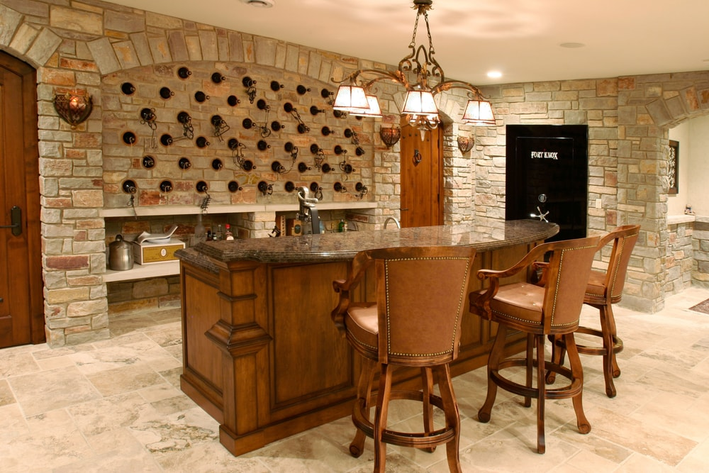 An ornate basement home bar area with marble counter top, plush ...