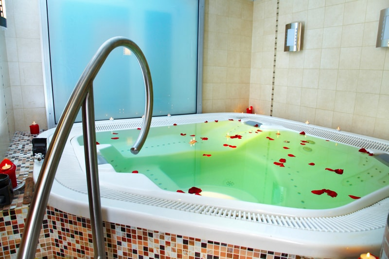 A Bath of a jacuzzi with petals of roses min - 27 Home Hot Tubs and Spa Pools