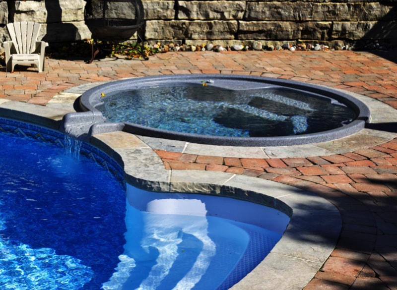 Backyard Swimming Spot : Outdoor inground residential swimming pool in a paved backyard with