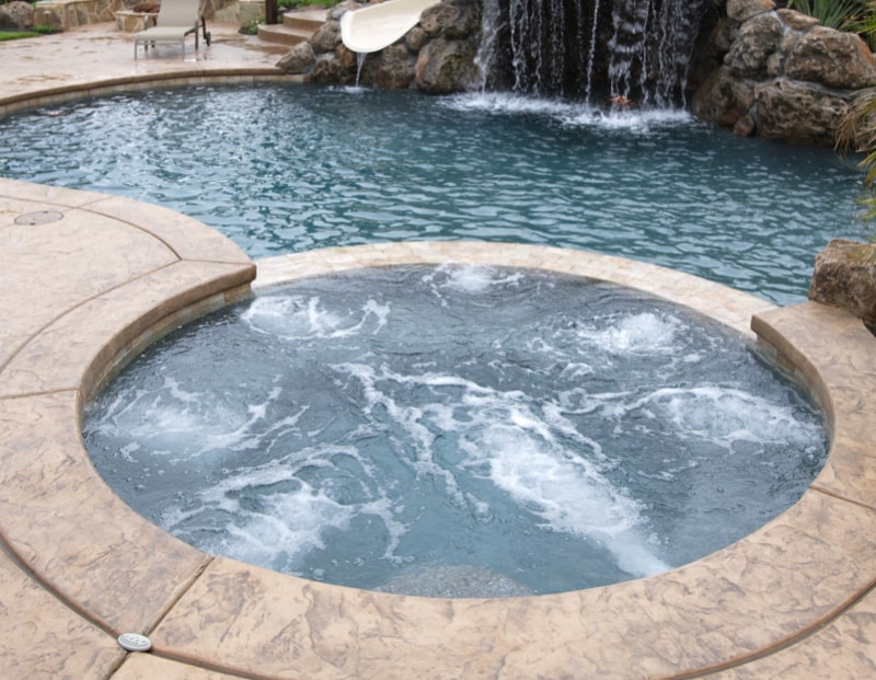 A waterfall in to a hot pool in a luxury backyard with tropical landscaping min - 27 Home Hot Tubs and Spa Pools