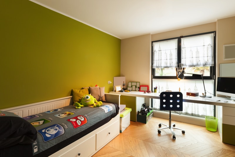 Boys room with green wall, timber parquet floor, large desk and a simple comfortable built in bed with base drawers