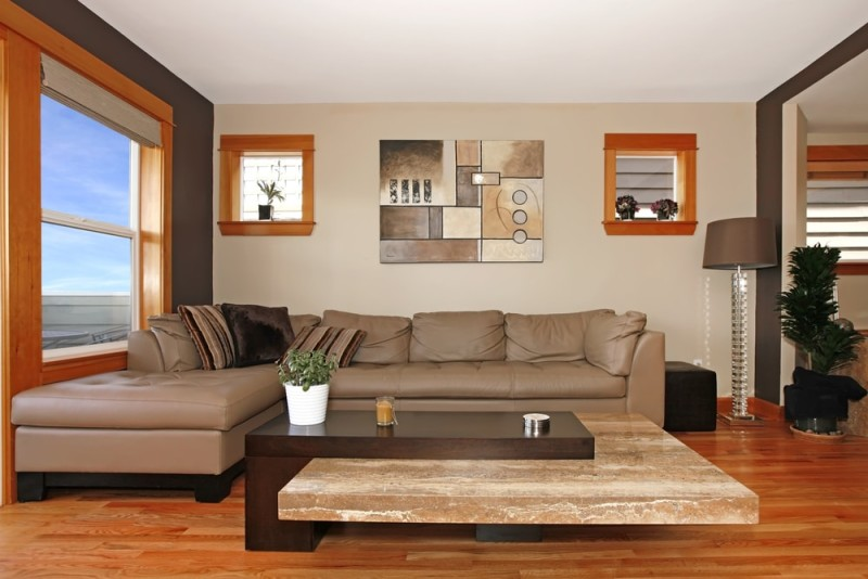 Modern living room interior with large and small windows, neutral wall colors and honey rich colored timber flooring