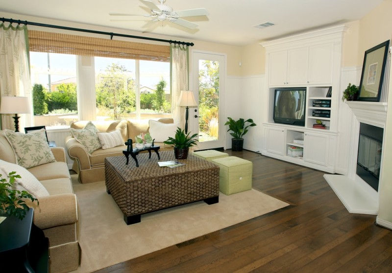 Contemporary living room is finished in earthy tones, and looks resplendent with its honey colored timber flooring