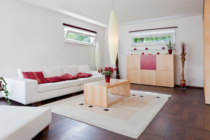Modern house living room with a contemporary white leather sofa and beautiful parquet woden floor