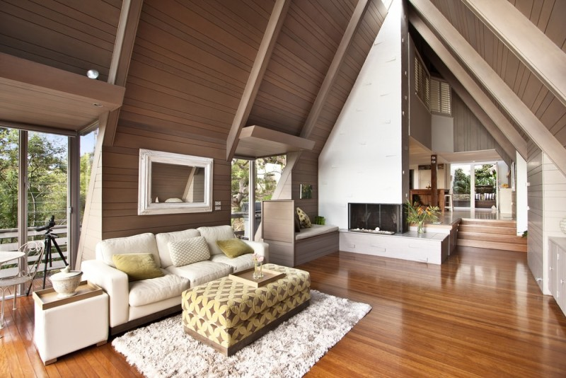 A modern living room with stained cathedral ceilings and contrasted against the beautiful honey glow of the timber floor