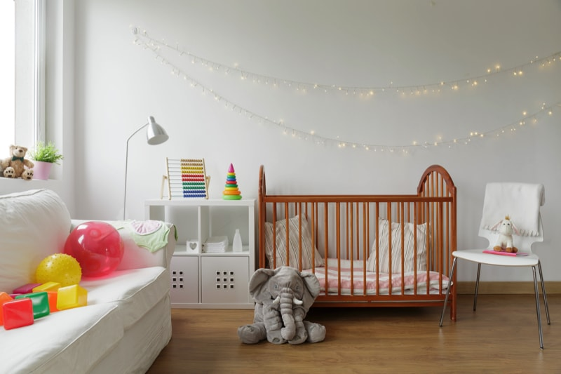 Newborn child's room with white walls and wooden bed