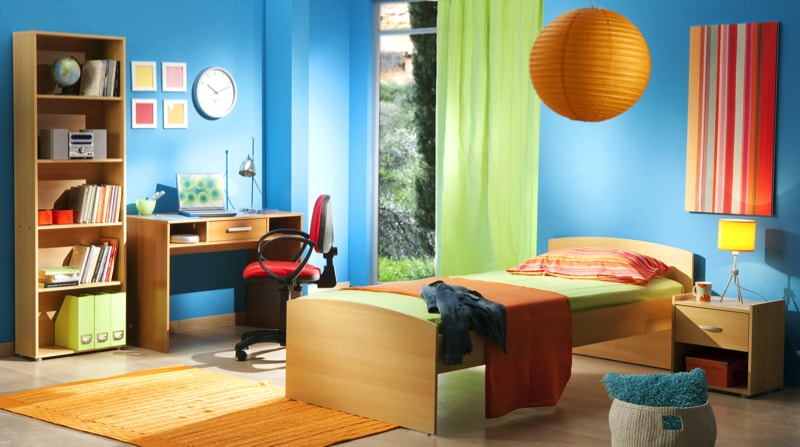 Vibrant and light filled child's room with blue walls that contrast well with pale wooden floor
