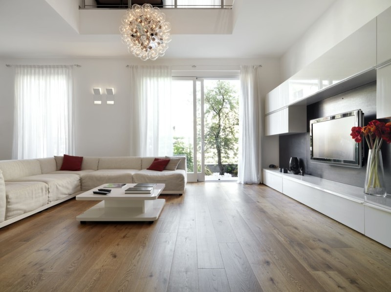 An expansive modern living room with light colored wooden flooring