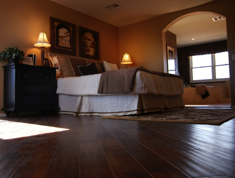 luxury bedroom with dark hardwood flooring in a room with darkish