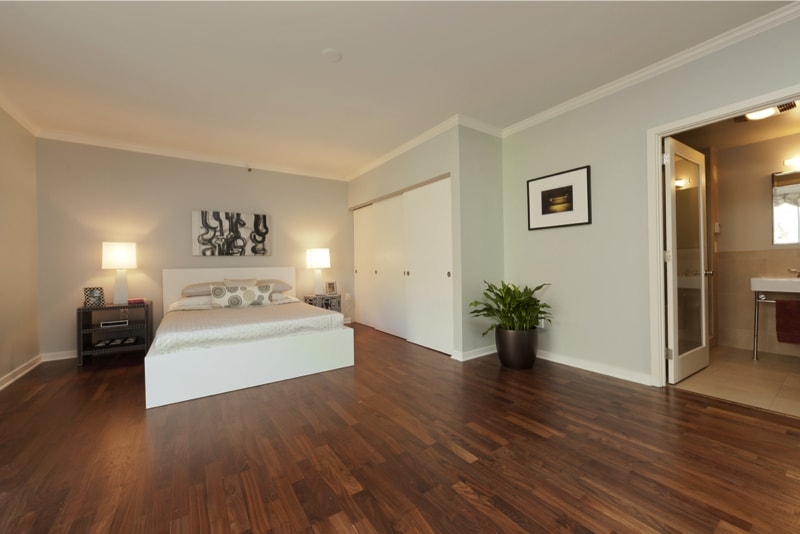 modern large bedroom with dark hardwood flooring grey walls and